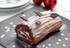 Yule log cake on a Christmas table Royalty Free Stock Images