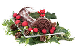 Yule Log. Christmas chocolate yule log cake with red baubles and holly over white background Royalty Free Stock Photos