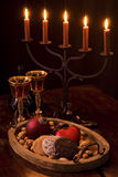 Yuletide. Candle holder with Christmas plate and red wine on wooden table with black background Royalty Free Stock Photos