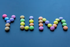 Yum spelled out with coated chocolate candy Royalty Free Stock Photos