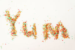 Yum spelt out in sugar candy sprinkles Stock Images