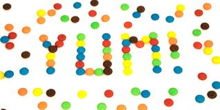 Yum word written with colorful button shaped chocolates candy is Stock Photo