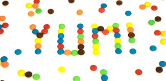 Yum word written with colorful button shaped chocolates candy is Royalty Free Stock Images