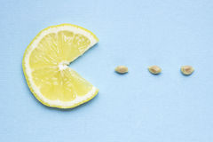 Yum-yum. Creative concept photo of a lemon slice eating seeds on blue background Stock Photos
