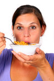 Yummie!. A young woman enjoys her crunchy cornflakes. Isolated over white Royalty Free Stock Images