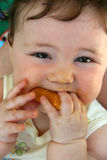 Yummie Mummie!. Baby eating a cookie. 'Could eat my fingers with that stock image
