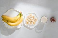 Yummy μπανάνες και κύπελλο με τις φέτες στο ξύλινο υπόβαθρο στοκ φωτογραφίες