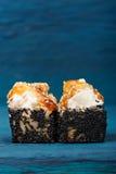 Yummy ρόλοι σουσιών με το τυρί κρέμας και τη σάλτσα καραμέλας στο μαύρο τ Στοκ εικόνα με δικαίωμα ελεύθερης χρήσης