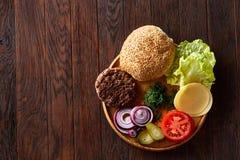 Yummy ингридиенты гамбургера художнически организованные на деревянной плите, конце-вверх, взгляд сверху, селективном фокусе Стоковое Изображение