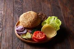 Yummy ингридиенты гамбургера художнически организованные на деревянной плите, конце-вверх, взгляд сверху, селективном фокусе Стоковое фото RF