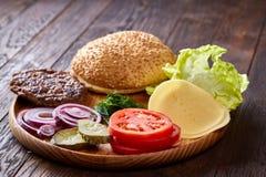 Yummy ингридиенты гамбургера художнически организованные на деревянной плите, конце-вверх, взгляд сверху, селективном фокусе Стоковое Изображение RF