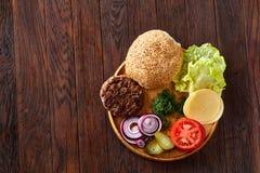 Yummy ингридиенты гамбургера художнически организованные на деревянной плите, конце-вверх, взгляд сверху, селективном фокусе Стоковое Фото