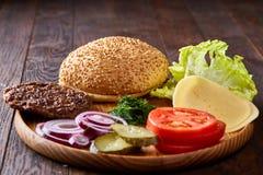Yummy ингридиенты гамбургера художнически организованные на деревянной плите, конце-вверх, взгляд сверху, селективном фокусе Стоковые Изображения RF