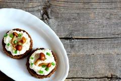 Yummy канапе с мягким сыром и лисичкой величает на плите на деревянной предпосылке Стоковые Фотографии RF