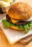 Yummy место гамбургера говядины и сыра на деревянном подносе около картошки Стоковая Фотография RF