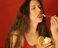 Yummy!. Enjoying dessert. DOF with focus on the teaspoon. woman is in soft focus royalty free stock photo
