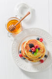 Yummy american pancakes with maple syrup and berries. Closeup of yummy american pancakes with maple syrup and berries royalty free stock photography