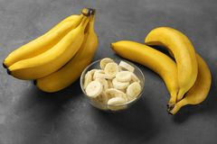 Yummy bananas and bowl with slices Royalty Free Stock Images