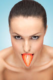 Yummy berry. A creative portrait of a beautiful girl holding a fresh strawberry in her sexy mouth like a tongue Stock Photography