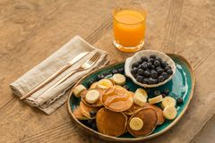 Yummy breakfast. Pancakes with blueberries, banana and fresh ora Royalty Free Stock Photo