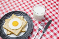 Yummy breakfast on the table. Top view of yummy breakfast with fried egg, breads and milk on the table Stock Image