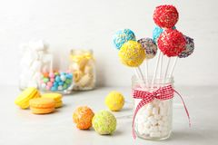 Yummy Bright Cake Pops In Glass Jar Full Of Marshmallows On Table Royalty Free Stock Photography