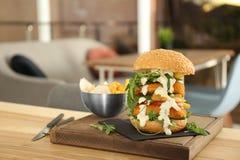 Yummy burger που εξυπηρετείται τεράστιο στον πίνακα στον καφέ στοκ φωτογραφία με δικαίωμα ελεύθερης χρήσης