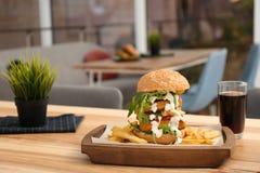 Yummy burger που εξυπηρετείται τεράστιο στον πίνακα στον καφέ στοκ εικόνες