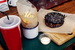 Yummy burger. serving cheeseburger or hamburger with cola and fr. Ench fries on wooden desk. catering in food court at mall concept. space for text. modern Royalty Free Stock Images