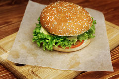 Yummy burger. serving cheeseburger or hamburger with salad and t Royalty Free Stock Images