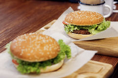Yummy burger. serving cheeseburger or hamburger with salad tomat. Oes onion  on wooden desk. catering in food court at mall concept. space for text. modern Stock Photos