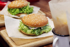 Yummy burger. serving cheeseburger or hamburger with salad tomat. Oes onion  on wooden desk. catering in food court at mall concept. space for text. modern Stock Images