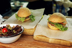 Yummy burger. serving cheeseburger or hamburger with salad on wo. Oden desk. catering in food court at mall concept. space for text. modern kitchen Royalty Free Stock Photo