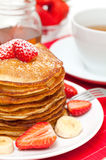 Yummy buttermilk pancakes. Breakfast with yummy buttermilk pancakes decorated by the strawberries Royalty Free Stock Photography