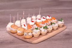 Yummy catering on wooden table. Nice decorated catering on a wooden plate Royalty Free Stock Image