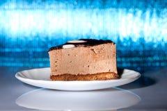 Yummy chocolate cake on blue background. Yummy chocolate cake on shiny blue background. Shallow focus Stock Photo