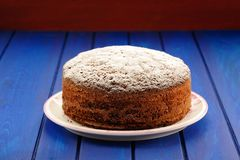 Yummy chocolate fruit cake with icing sugar on blue table Stock Images