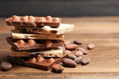 Yummy chocolate pieces with hazelnuts. On wooden table Stock Image
