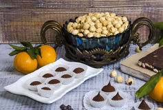 Yummy chocolate sweets with hazel nut and tangerines Royalty Free Stock Photography