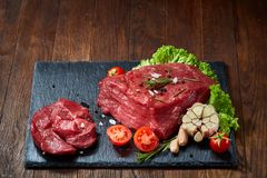 Composition of raw beefsteak on slate board with vegetables and seasoning, selective focus, close-up. Yummy composition of raw beefsteak on slate board with Royalty Free Stock Photos