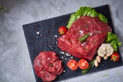 Composition of raw beefsteak on slate board with vegetables and seasoning, selective focus, close-up, top view. Yummy composition of raw beefsteak on slate board Royalty Free Stock Photos