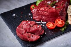 Composition of raw beefsteak on slate board with vegetables and seasoning, selective focus, close-up. Yummy composition of raw beefsteak on slate board with Stock Photography