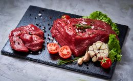 Composition of raw beefsteak on slate board with vegetables and seasoning, selective focus, close-up. Yummy composition of raw beefsteak on slate board with Stock Images