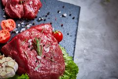 Composition of raw beefsteak on slate board with vegetables and seasoning, selective focus, close-up. Yummy composition of raw beefsteak on slate board with Royalty Free Stock Images