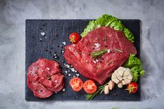 Composition of raw beefsteak on slate board with vegetables and seasoning, selective focus, close-up. Yummy composition of raw beefsteak on slate board with Royalty Free Stock Photo