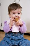 Yummy Cookie. Adorable child on the kitchen floor happily munching on a cookie royalty free stock photography