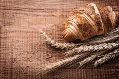 Yummy croissant bunch of wheat ears on oak wooden Stock Photo