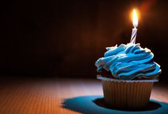 Cupcake with buttercream and burning candle on wooden table against dark background with copy space. Royalty Free Stock Images