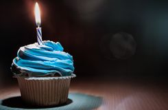 Cupcake with buttercream and burning candle on wooden table against dark background with copy space. Yummy cupcake with buttercream and burning candle on wooden royalty free stock photo