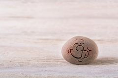 Yummy emoticon. Stone face on white wood background with free space for your text Stock Photo